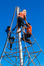 Children climbing spider rope apparatus at durbans peoples park playground in the blue sky for development Stock Photos