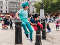 Children in colorful clothes play on iron railings in Trafalgar Royalty Free Stock Photo