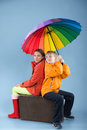 Children with a colorful umbrella girl and boy sitting on an old traveling bag studio shot on blue background Royalty Free Stock Photo