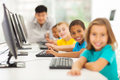 Children computer class smiling group in with teacher on background Royalty Free Stock Photo