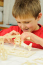 Children creativeness smart young child building a wooden helicopter model from a kit Stock Photography