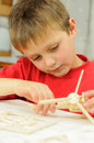 Children creativity smart young child building a wooden helicopter model from a kit Stock Image
