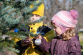 Children decorating New Year tree with toy balls Royalty Free Stock Images