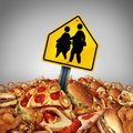 Children diet problems and obesity crisis in the school concept as a heap of unhealthy fast food with two overweight fat kids on a Stock Images