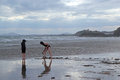 Children digging on a cloudy beach two one is in the sand the other wearing coat and hood is watching castle is in the Stock Image