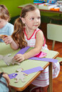 Children doing arts crafts in a group at the table in kindergarten Stock Photos