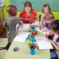 Children drawing with nursery interracial group of teacher in kindergarten Royalty Free Stock Photos