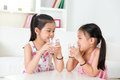 Children drinking milk asian family at home beautiful sister drinks together Stock Photos
