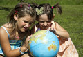 Children with earth globe girls looking the Stock Photography