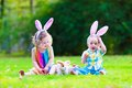 Children at easter egg hunt two little cute curly toddler girl and funny baby boy wearing bunny ears having fun playing with Royalty Free Stock Photos