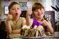 Children eat a cake sit near table and Royalty Free Stock Photography