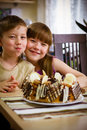 Children eat a cake sit near table and Stock Photography