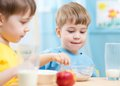 Children eat healthy food at home or kindergarten