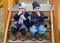 Children eating apples at playground two small boys brothers sitting on the steps in a and Stock Image