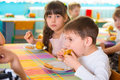 Children eating baked apple and cookie at daycare Royalty Free Stock Photo