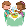 Children eating healthy food two sitting on the table enjoy a salad and drinking water and juice Royalty Free Stock Photo