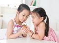 Children eating ice cream cone asian sharing an beautiful girls model at home Royalty Free Stock Photography