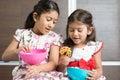 Children eating snacks two cute indian girls traditional snack murukku asian sibling or enjoying food living lifestyle at home Stock Photos