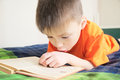 Children education, boy reading book lying on bed, child portrait with book, interesting storybook Royalty Free Stock Photo