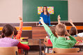 Children in elementary school are raised hand in classroom teacher is the background front of chalkboard Stock Images