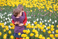 Children embrace each other on  field of tulips Stock Photos