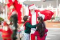 Children embracing santa claus happy in courtyard Royalty Free Stock Photos