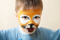 Children face painting. Boy painted as tiger or ferocious lion by make up artist. Preparing for theatrical performance