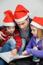 Children and father reading book in santa hats at home Royalty Free Stock Photos