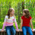 Children friend girls talking on the jungle park forest sister friends relaxed sitting outdoor Royalty Free Stock Photos