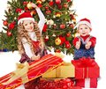 Children with gift box near Christmas tree. Royalty Free Stock Image