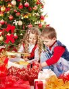 Children with gift box near Christmas tree. Royalty Free Stock Photos
