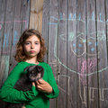 Children girl holding puppy dog on backyard wood fence Royalty Free Stock Photo