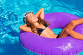 Children girl relaxed on purple inflatable pool ring Royalty Free Stock Images