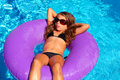 Children girl relaxed on purple inflatable pool ring Royalty Free Stock Photo