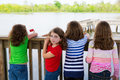 Children girls back looking at lake on railing rear view and one behind Royalty Free Stock Images