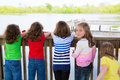 Children girls back looking at lake on railing rear view and one behind Stock Images