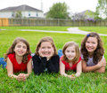 Children girls group lying on lawn grass smiling happy together in a row Stock Photos