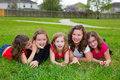 Children girls group lying on lawn grass smiling happy together in a row Royalty Free Stock Images