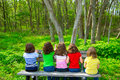 Children girls sitting on park bench looking at forest sister and friend rear view Royalty Free Stock Photos