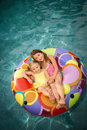Children girls swim pool or in inner tube floating in water Stock Images