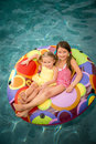 Children girls swimming pool or in inner tube floating in water Stock Photography