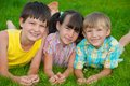 Children on green grass three smiling Stock Image