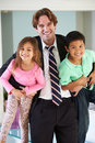 Children greeting father on return from work smiling to camera Stock Image
