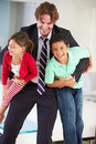 Children greeting father on return from work smiling to camera and Stock Photography