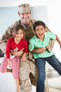 Children greeting military father home on leave smiling to camera Royalty Free Stock Image