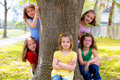 Children group of sisters girls and friends on tree trunk playing at the park outdoor Stock Photography