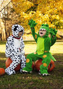 Children in halloween costumes having fun two boys laughing and joking sitting together on pumpkins while outfitted dragon and dog Royalty Free Stock Photography