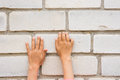 Children hand trying to grab the tabs brick wall Royalty Free Stock Photo