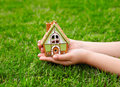 Children hands hold a house on a background of green grass small Royalty Free Stock Image