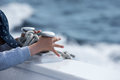 Children hands while holding boat bollard on blue sea background Royalty Free Stock Image